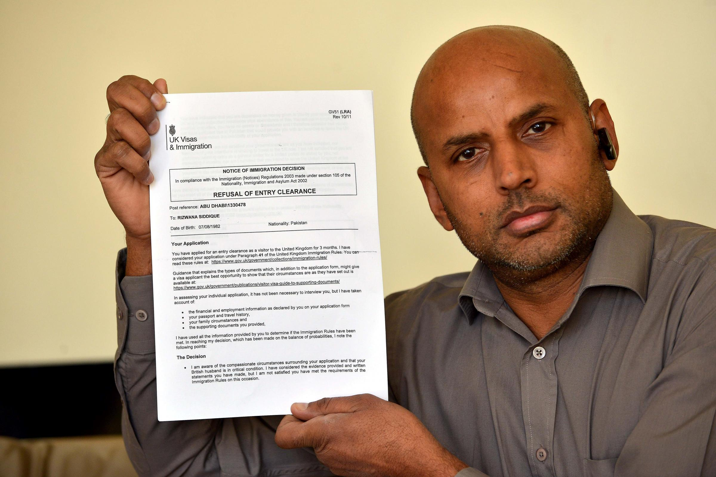 Mohammed Ramzan, uncle of Haq Nawaz Rasool, holds aloft a letter refusing Haq's wife - 3519358